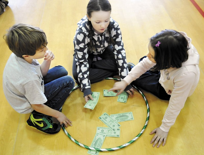 Sullivan Anderson, Miranda Northrup, center, and Abby Peaslee count play money during a game in physical education class at Whitefield Elementary School in Whitefield on Feb. 26.