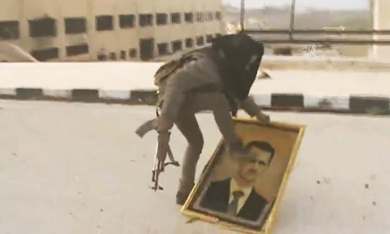 A Syrian rebel fighter stomps on a picture of Syrian President Bashar Assad after rebels seized the police academy complex in Khan al-Asal, in the province of Aleppo, Syria, on Sunday.