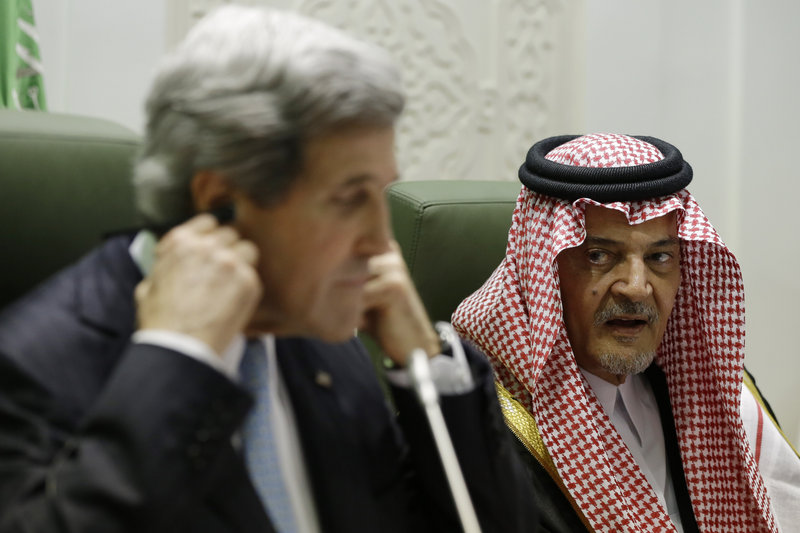 Secretary of State John Kerry adjusts his translation headset as Saudi Foreign Minister Prince Saud al-Faisal speaks during a news conference in Riyadh, Saudi Arabia, on Monday.