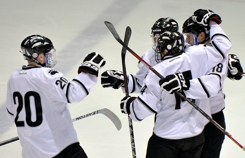 John McGinnis, left, celebrates Bowdoin's first goal Wednesday scored by Jay Livermore, 18, in the first period at Brunswick. Bowdoin won, 5-2.