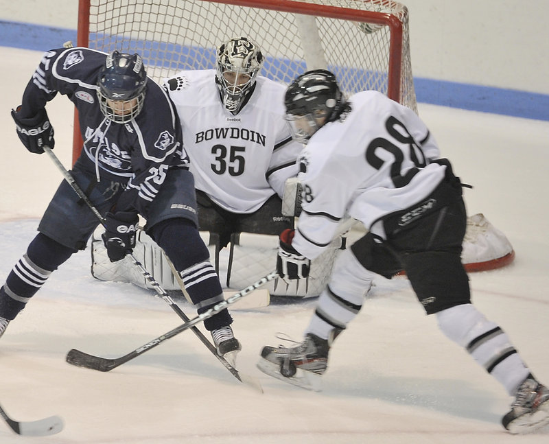 Bowdoin's Timothy McGarry battles with Shaun Walters of UMass-Dartmouth in front of goalie Steve Messina Wednesday in an NCAA Division III playoff game.