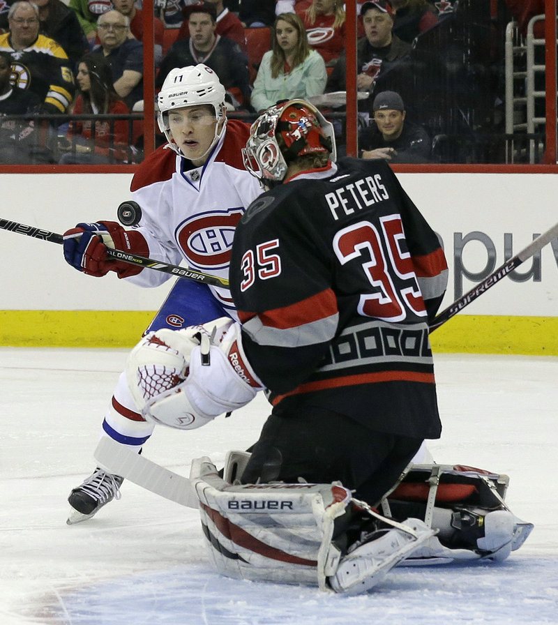 Montreal's Brendan Gallagher tries to bunt the puck past Carolina goaltender Justin Peters during Thursday's game in Raleigh, N.C., won by the Canadiens.