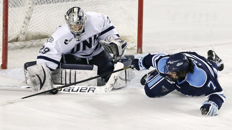 New Hampshire goalie Casey DeSmith makes a save as Maine's Ryan Lomberg stabs at the puck during Friday's game in Durham, N.H. Maine won at the Whittemore Center for the first time since 2005.