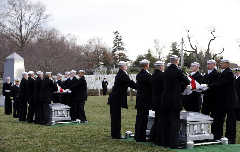 A pair of Navy Honor Guard teams carry two caskets of remains on Friday, as they depart Fort Meter Memorial Chapel during services to honor two sailors from the USS Monitor in Arlington National Cemetery. Identities of the remains were not clearly established.
