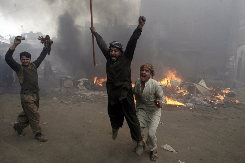 Pakistani men react after burning belongings of Christians in Lahore on Saturday over accusations that a Christian man committed blasphemy against Islam's Prophet Muhammad.