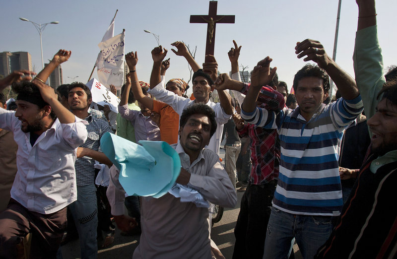 Pakistani Christians in Islamabad chant slogans at a protest Sunday demanding that the government rebuild their homes, which were burned following an alleged blasphemy incident.