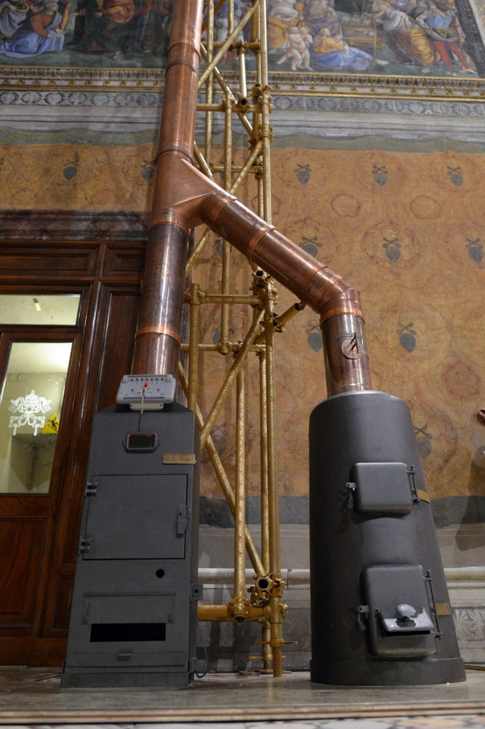 "The stoves where the ballots will be burned are shown inside the Sistine Chapel. A chimney will pipe out puffs of smoke to tell the world if there's a new pope. Black smoke means ""not yet."" White smoke means ''pope elected."" When Vatican firefighters hoisted the chimney to its perch, it was a visual cue that preparations for the conclave to elect retired Pope Benedict XVI's successor were in high gear."