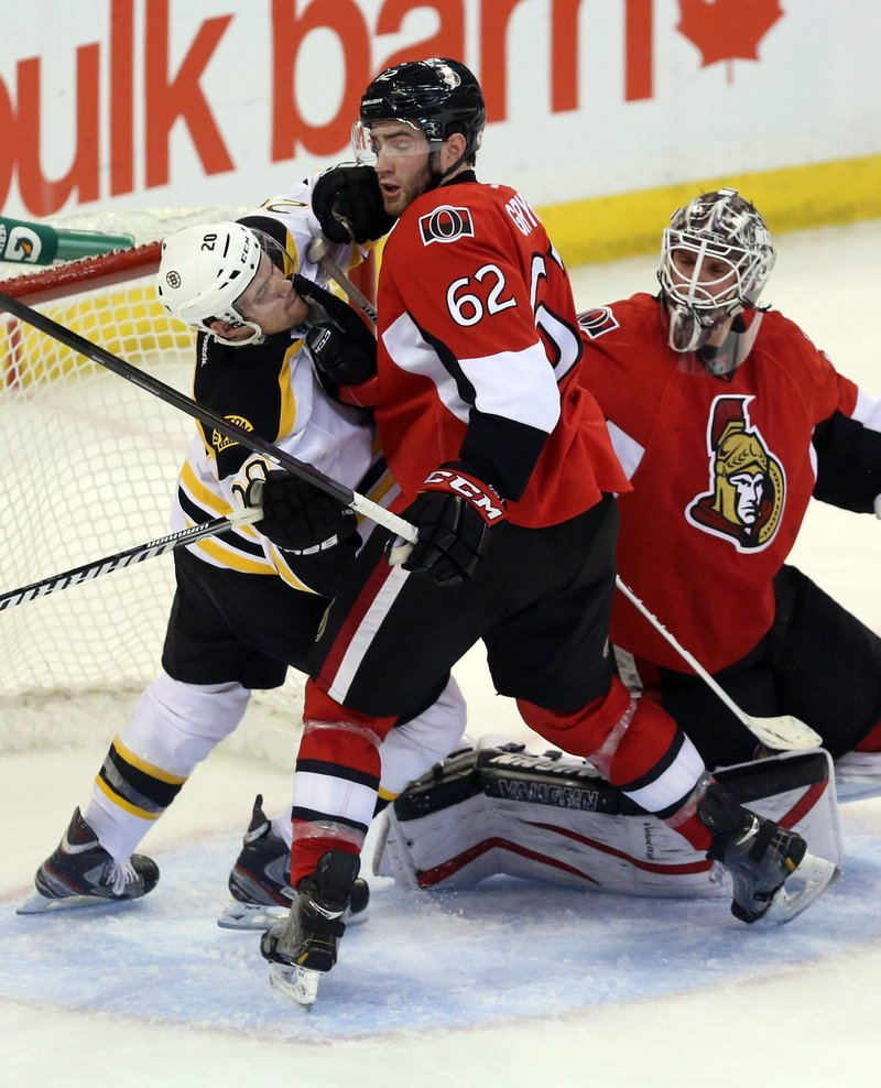 Eric Gryba of Ottawa walks into the fist of Boston's Daniel Paille during a scramble in front of Senators goalie Robin Lehner Monday night in Ottawa.