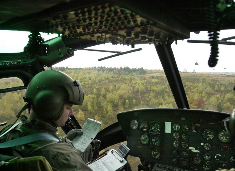 In this October 2001 file photo, Dean Dumond, a helicopter pilot with the 1st of the 137th Aviation Battalion of the Maine Army National Guard, checks flight notes while flying over Canadian Forces Base Gagetown in New Brunswick, Canada.