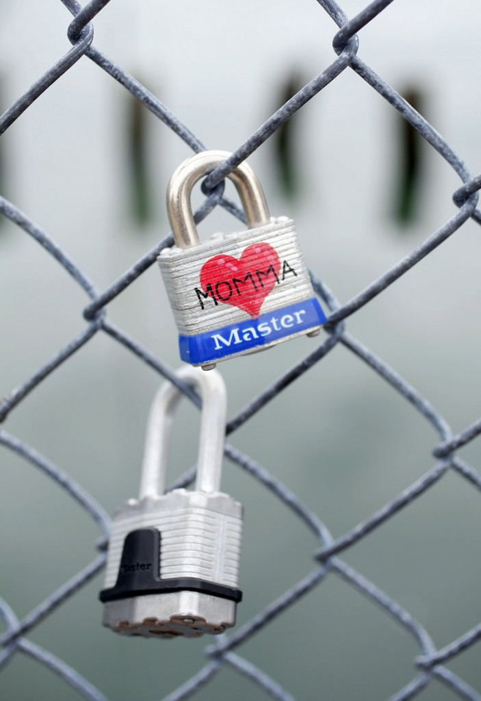 """A padlock dedicated to """"Momma"""" joins the dozens of other locks on the Commercial Street fence."""