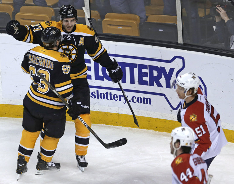 Boston center Patrice Bergeron is congratulated by linemate Brad Marchand, 63, after a first-period goal against Florida in Thursday's game, won by the Bruins.