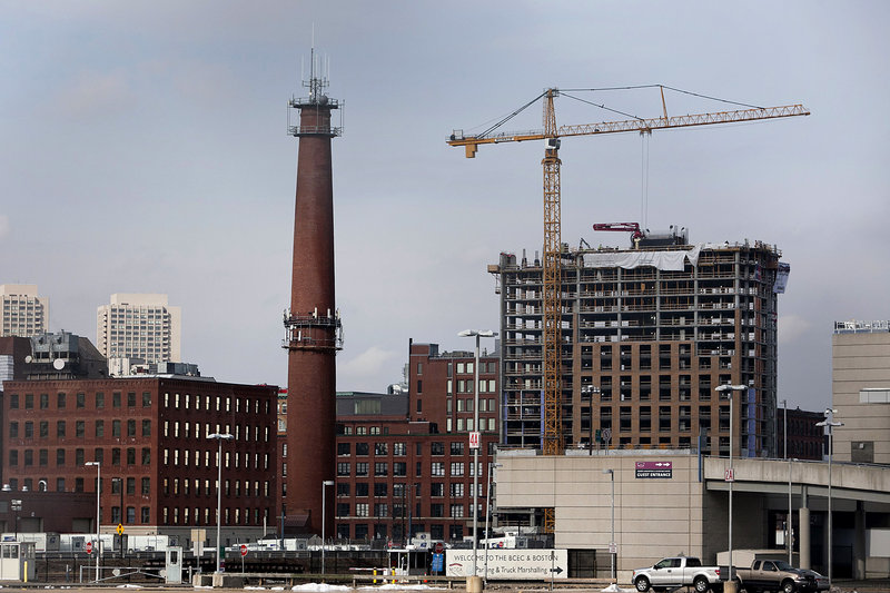 A crane stands on the top of a high-rise building under construction on A Street in Boston. Developers and investors drawn to Boston's expanding life sciences and technology industry, along with a growing work force of educated young adults, are fueling a boom in construction.