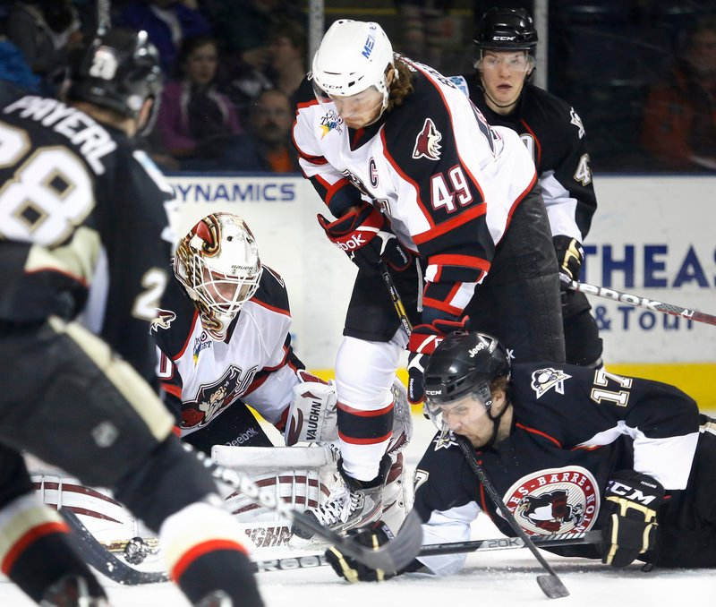 Portland goaltender Chad Johnson makes a save during first-period action of Saturday's game while teammate Alexandre Bolduc gives a stick-shave to a prone Paul Thompson.