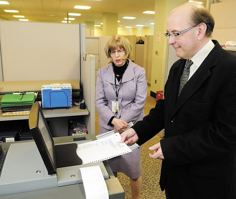 Deputy Secretary of State Julie Flynn, left, and Secretary of State Matt Dunlap demonstrate a vote tabulator last week in Augusta. Litchfield recently rejected a second offer by the state for a machine to tabulate state and federal election ballots in favor of continuing hand-counting.