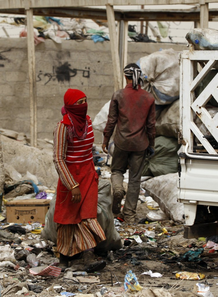 An Iraqi woman carries a bag of recyclable materials at a garbage dump in the Shiite enclave of Sadr City in Baghdad, Iraq, on Sunday. According to the manager of the dump, the people who salvage plastic and aluminum make an average of $8 per day re-selling the materials. The intractable nature of Baghdad politics has widened the country's ethnic and sectarian fault lines.