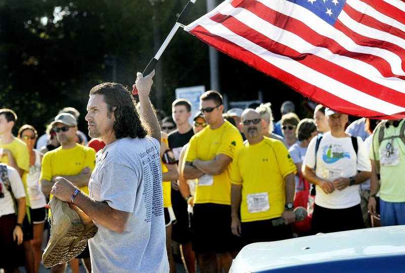 In this Aug. 19, 2012 file photo, Carlos Arredondo of Boston waves a flag and holds the boots of his fallen son, Lance Cpl. Alexander Arredondo, 20, at the start of the Run for the Fallen in Ogunquit. Alexander died while serving in the Marine Corps in Iraq in 2004.