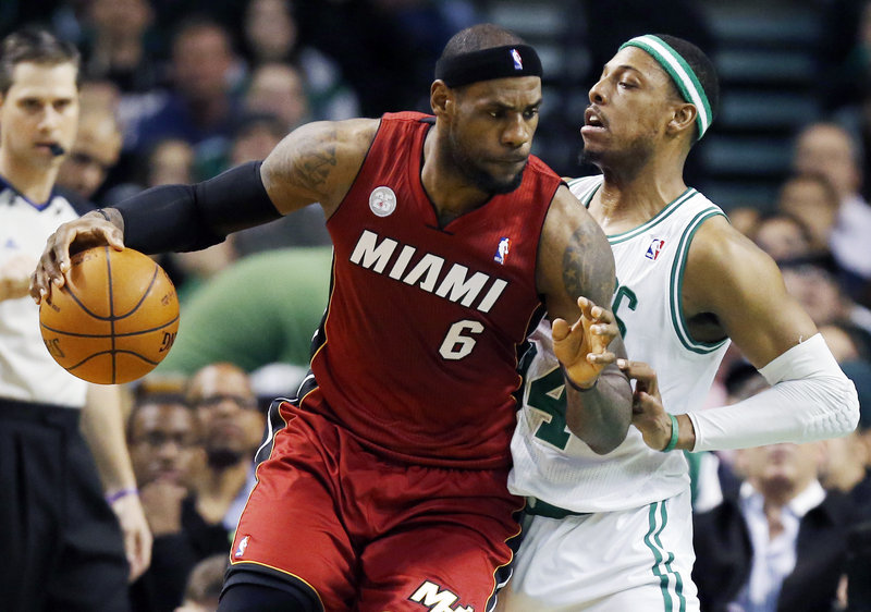 Miami's LeBron James puts his shoulder into Boston's Paul Pierce during the Heat's 105-103 win at Boston on Monday. Boston's Kevin Garnett sat out the game with the flu.