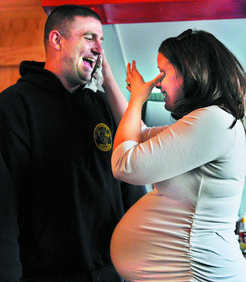 Megan McGuire and her husband, Travis, laugh on Wednesday March 20, 2013 moments after he surprised her by returning early from an Army deployment in Afghanistan to be present for the birth of their first child.