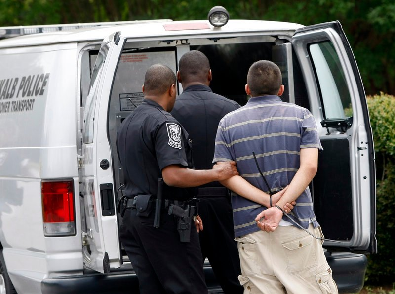 "A suspect is loaded into a DeKalb police prisoner transport van during a ""pill mill"" raid at Southern Health Management next to police headquarters near Tucker, Ga., in 2012."