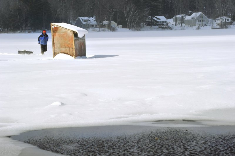 An ice fisherman on Kennebunk Pond in Lyman on Wednesday makes his way to his ice-fishing shack, which was located about 100 yards from open water near the public boat launch.