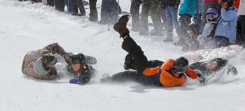 The team known as The Bed Bugs, Tim Hiltz, left, and his sons Brayden, Logan and Dillon, left to right, hit the snow after falling off their mattress while competing at Shawnee Peak in Bridgton on Saturday. The team came in fifth place.