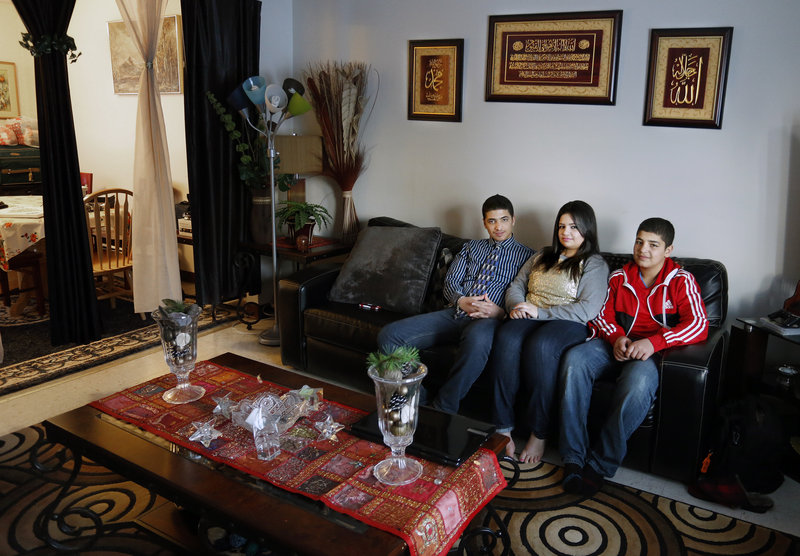 Ahmed, 14, Sandra, 17, and Mohammed Banijameel, 12, sit in their Westbrook home. The Banijameel family, originally from Iraq, moved to Westbrook after living in Portland.