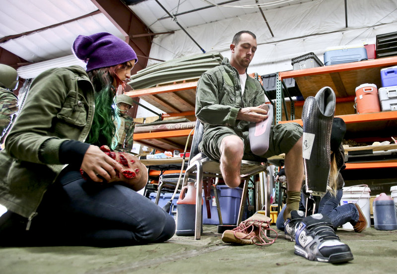 Former Navy corpsman Joel Booth, who lost a leg in Afghanistan, prepares with the help of a makeup artist to play his role as a downed helicopter pilot in a military training exercise at San Diego-based Strategic Operations.