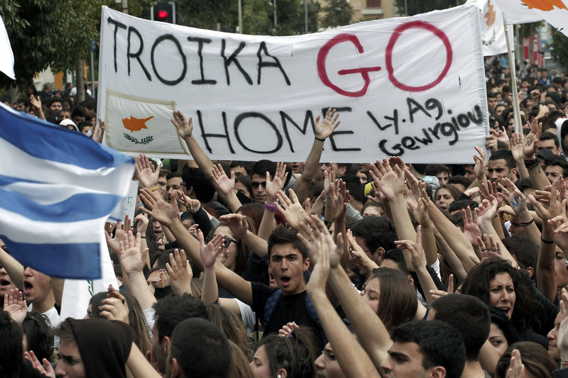Cypriot students shout slogans near the presidential palace in the capital of Nicosia on Tuesday. Banks across Cyprus remained closed on Tuesday.