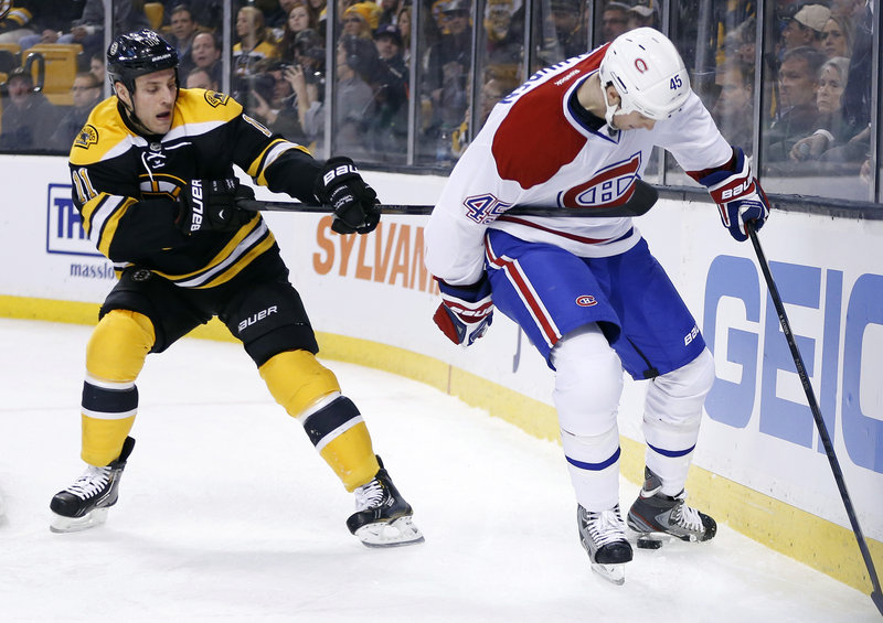 Gregory Campbell of the Bruins hooks Montreal's Michael Blunden in the first period Wednesday night in Boston. The Canadiens rallied, then won in a shootout, 6-5.