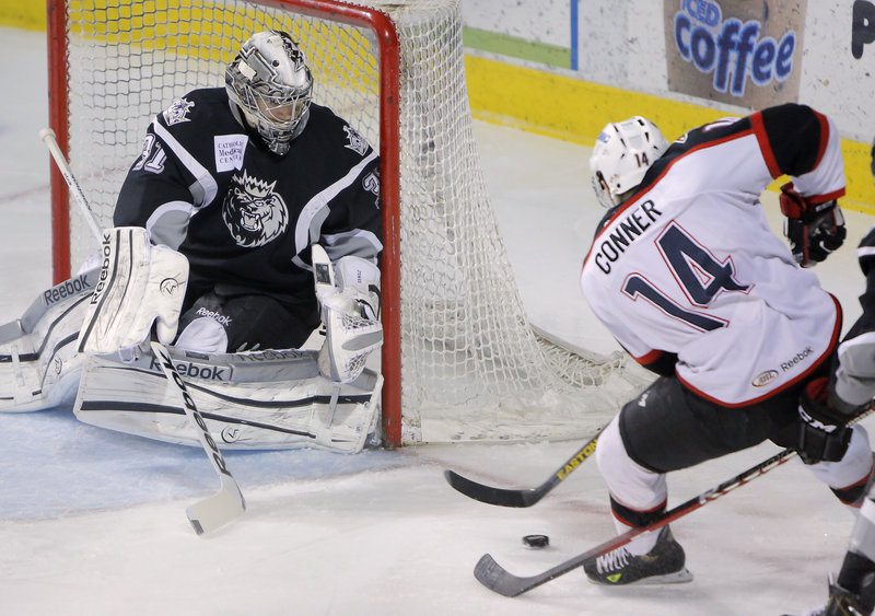 Chris Conner of the Pirates looks to work the puck past Manchester Monarchs goalie Martin Jones. Portland won 6-3 at the Cumberland County Civic Center.