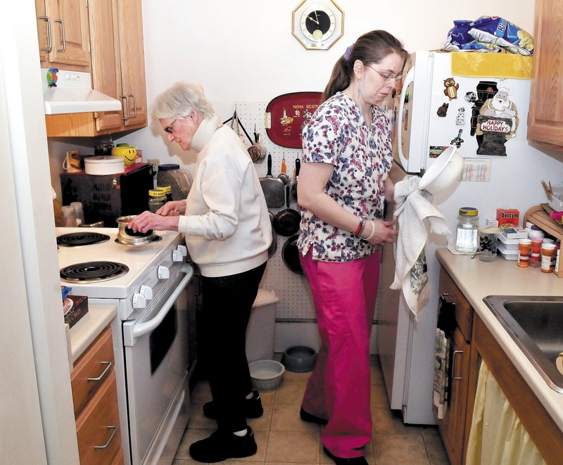 Waterville resident Marie Rouleau, 84, left, and Zandra Luce, a personal support specialist, work in the kitchen preparing a meal. Rouleau is on a waiting list for Meals on Wheels.