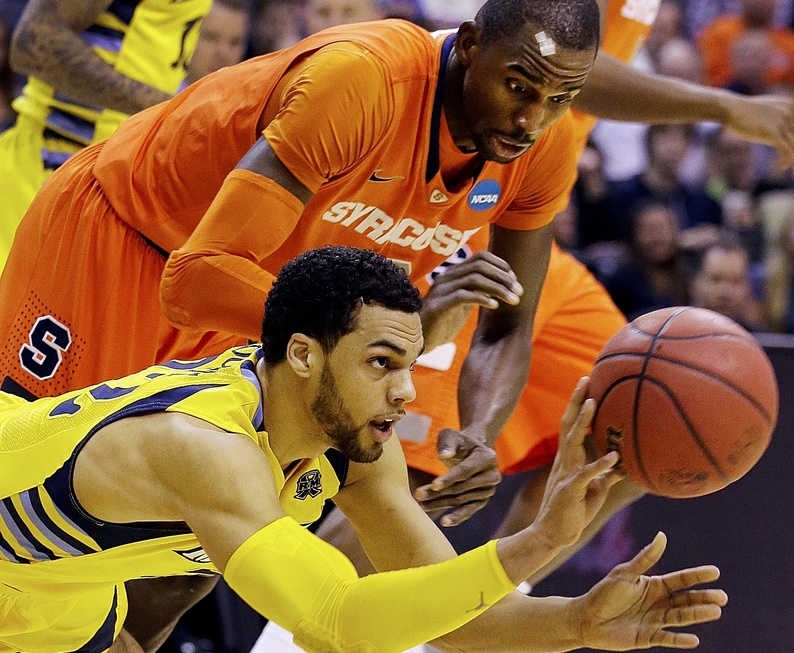Marquette guard Trent Lockett (22) passes the ball away from Syracuse center Baye Keita (12) during the first half of the East Regional final in the NCAA men's college basketball tournament,Saturday in Washington.
