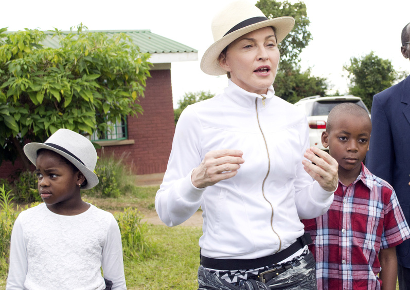 Pop singer Madonna tours an orphanage last week near Lilongwe, the capital, with children she adopted in Malawi, David Banda, right, and Mercy James.