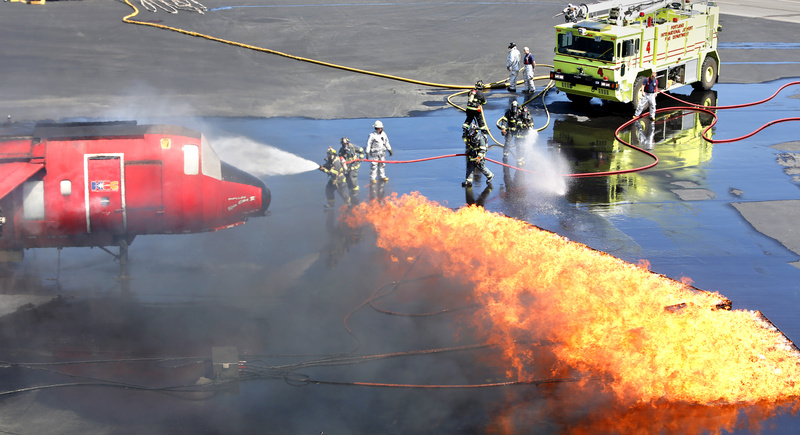 Firefighters conduct an annual FAA training exercise for responding in case of a fire on board a plane at the Portland International Jetport in Portland on Tuesday.