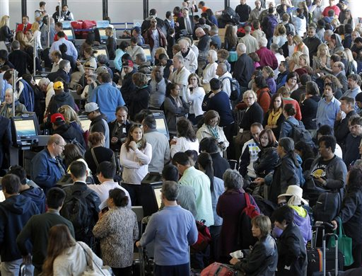Passengers gather at the American Airlines check-in for flights at Los Angeles International Airport on Tuesday. Computer problems forced American Airlines to ground flights across the country after the airline was unable to check passengers in and book passengers.