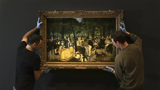 Employees of the Royal Academy of Art move a Manet painting at the Royal Academy of Arts in London. On April 11, films about art exhibitions from around the world will open in select movie theaters and performing arts centers in nearly 30 countries.