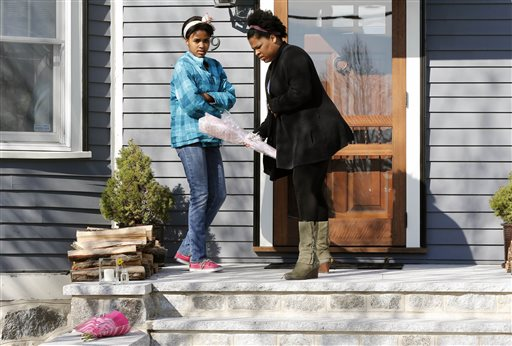 Two women place flowers on the doorstep of the Richard house in the Dorchester neighborhood of Boston on Tuesday. Martin Richard, 8, was killed in Monday's bombings at the finish line of the Boston Marathon. His mother, Denise, and 6-year-old sister, Jane, were badly injured.
