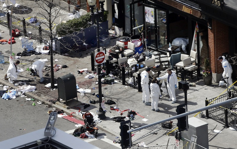 Investigators in haz-mat suits examine the scene of the second bombing on Boylston Street in Boston Tuesday, April 16, 2013 near the finish line of the 2013 Boston Marathon, a day after two blasts killed three and injured over 170 people. (AP Photo/Elise Amendola)