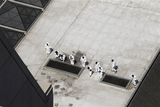 Investigators on Thursday inspect the roof of a building across the street from the area where a bomb exploded near the Boston Marathon finish line,