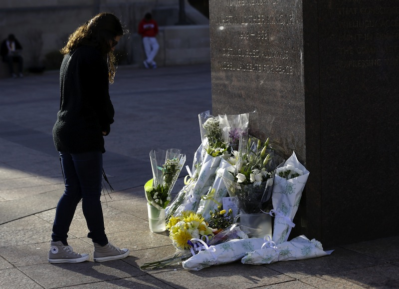 A woman reflects in front of a makeshift memorial honoring Boston University student Lingzi Lu, who was killed in the Boston Marathon explosions, Wednesday, April 17, 2013, in Boston. The city continues to cope following Monday's explosions near the finish line of the marathon, which claimed three lives. (AP Photo/Julio Cortez)