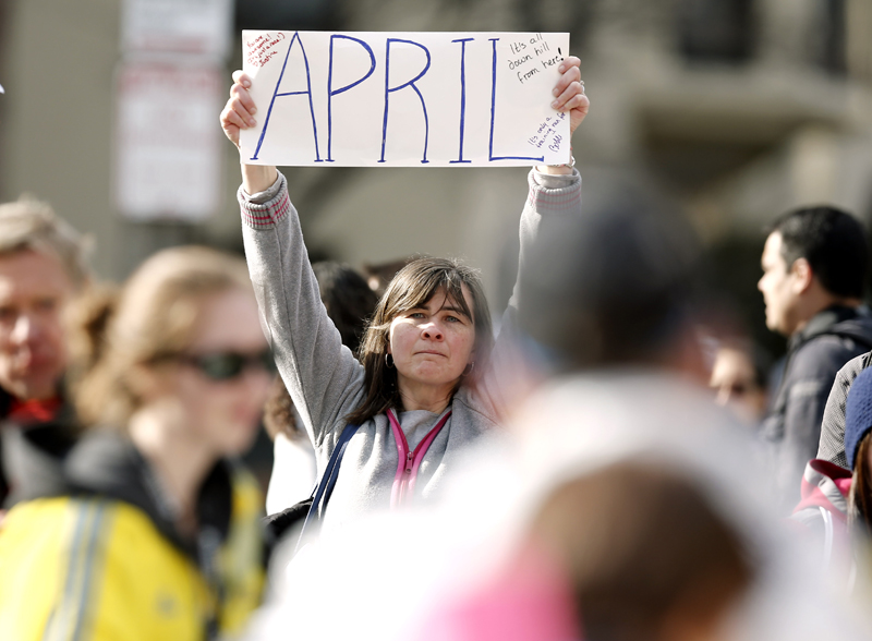 Justine Franco of Montpelier, Vt., holds up a sign near Copley Square in Boston looking for her missing friend, April, who was running in her first Boston Marathon Monday, April 15, 2013. Two bombs exploded near the finish line of the marathon on Monday, killing at least two people and injuring at least 23 others. (AP Photo/Winslow Townson)