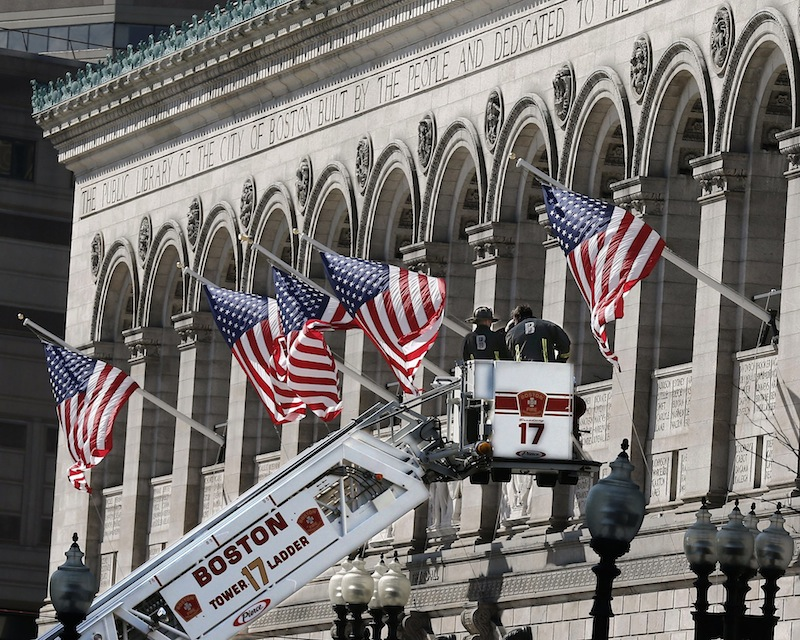 Responders search the area around the Boston Public Library near the finish line of the Boston Marathon with a ladder truck in Boston Tuesday, April 16, 2013. Two bombs blew up seconds apart Monday at the finish line of one of the world's most storied races, tearing off limbs and leaving the streets spattered with blood and strewn with broken glass. At least three people were killed, including an 8-year-old boy, and more than 170 were wounded. (AP Photo/Winslow Townson)