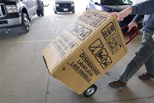An employee carts a dishwasher to a customer's vehicle recently at Nebraska Furniture Mart in Omaha, Neb.