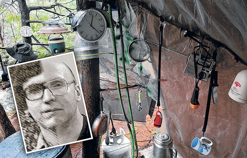 Coffee cups, lights and a clock hang under a tarp in Christopher Knight's camp in a remote, wooded section of Rome where he is thought to have lived since the 1990s. Police believe Knight, who went into the woods near Belgrade in 1986, committed hundreds of burglaries.