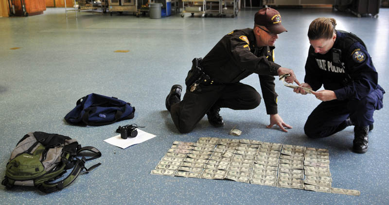 Somerset County Sheriff's Department Cpl. Gene Cole, left, helps Maine State Police Trooper Diane Perkins-Vance inventory money recovered from Christopher Knight on Tuesday at the Pine Tree Camp in Rome. Knight, a hermit who lived in the woods since April 1986, was apprehended when he broke into the camp, police claim. He was captured carrying a knapsack and bag of tools. Many of bills date from the 1980s and 1990s, Perkins-Vance said, and were never circulated by Knight.