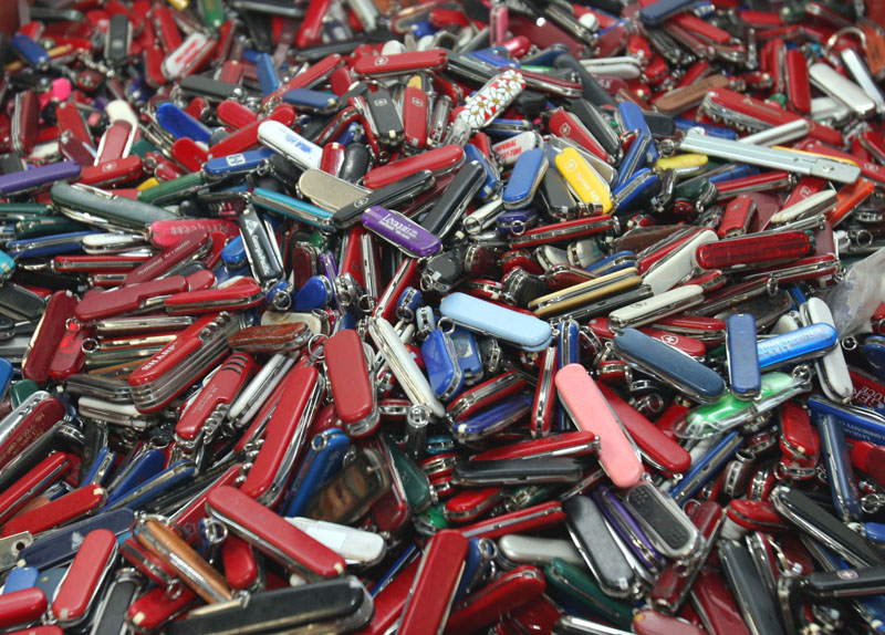 FILE - In this Sept. 26, 2006, file photo, knives of all sizes and types are piled in a box at the State of Georgia Surplus Property Division store in Tucker, Ga., and are just a few of the hundreds of items discarded at the security checkpoints of Hartsfield-Jackson Atlanta International Airport that will be for sale at the store. Federal officials say they�re delaying a policy that would allow passengers to carry small knives, bats, and other sports equipment onto airliners. The Transportation Security Administration said Monday, April 22, 2013, that the policy change has been delayed to accommodate feedback from an advisory committee made up of aviation industry, consumer, and law enforcement officials.(AP Photo/Gene Blythe, File)