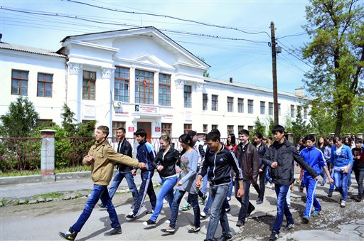 Schoolchildren march in front of a school where Tamerlan Tsarnaev, studied, in the small Kyrgyz city of Tokmok east of the country's capital of Bishkek.
