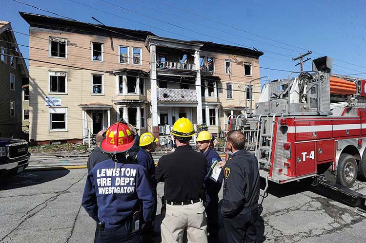 Lewiston fire officials and state fire marshals begin to investigate the scene of a fire that destroyed three apartment buildings in Lewiston on Monday.
