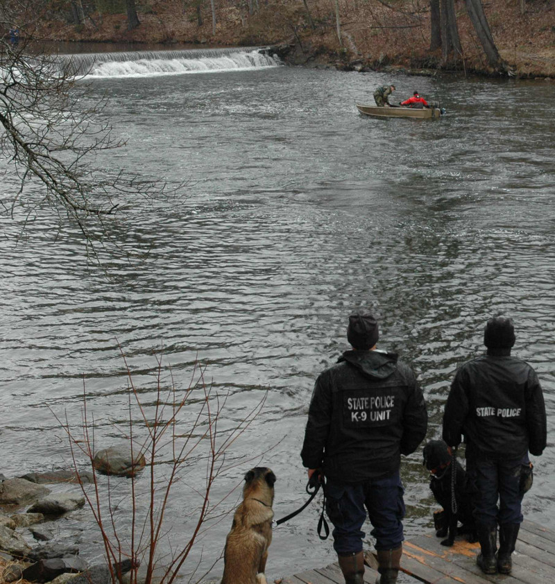 State police use a boat to recover the body of Romeo Parent, 20, from Jug Stream in East Monmouth on Friday. In the foreground are the state police dogs who discovered the body, and their handlers.