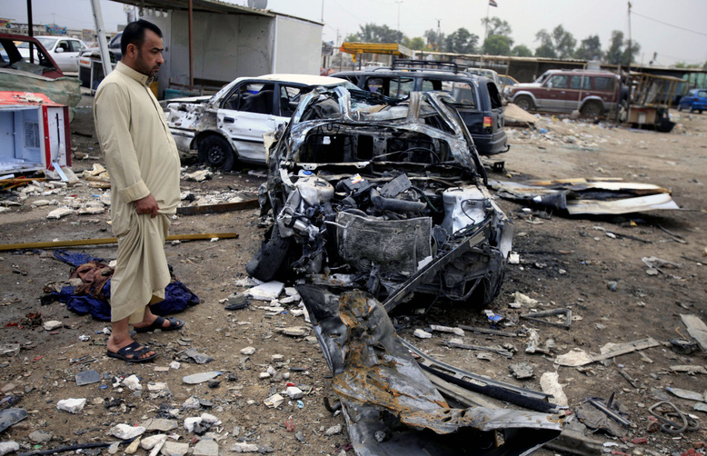 An Iraqi man inspects the aftermath of a car bomb attack at a used car dealer in eastern Baghdad, Iraq, on Tuesday. Violence is on the rise with the approach of Saturday's elections, the country's first since the 2011 U.S. troop withdrawal.